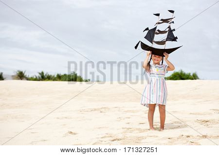 Cute little girl playing on the beach flying ship kite. Child enjoying summer family vacation at the sea.