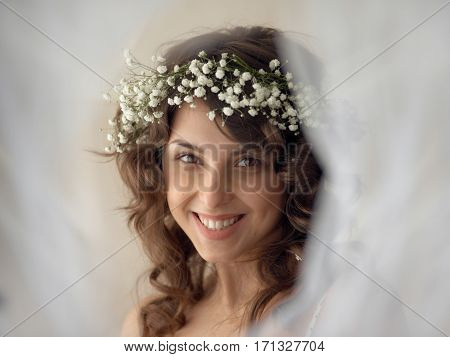 Beautiful woman with beaming smile wearing circlet of flowers