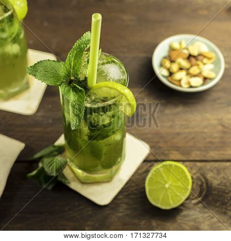 A square photo of a mojito cocktail with mint leaves, a wedge of lime, and a drinking straw, on a dark wooden background with copy space. Selective focus