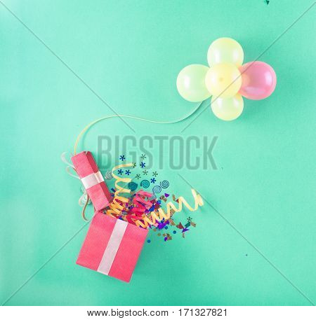 Red gift box with various party items and balloons. Celebration background. Top view