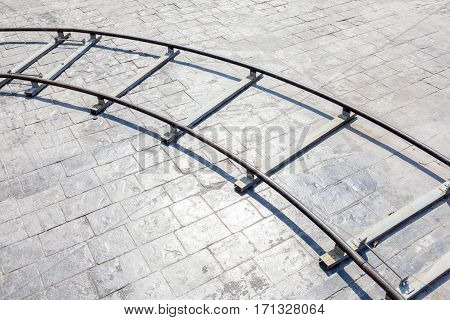 The curved part of metal dolly in outdoor location with brick floor background equipment usage for film industrial.
