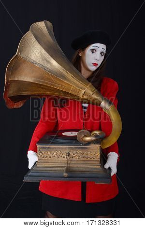 young brunette woman in a suit holding a mime uzykalnye old gramophone records for sound