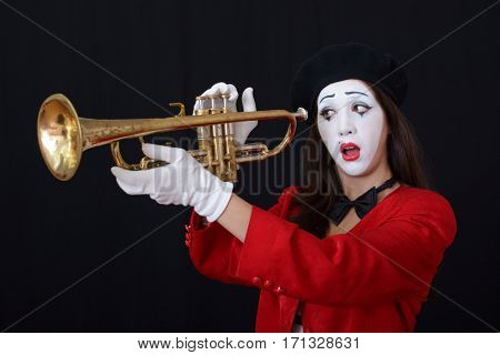 young brunette woman in a suit holding a mime pipe (wind instrument)