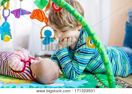 Happy little kid boy with newborn baby girl cute sister. Siblings. Brother and baby playing with colorful toys and rattles together. Kids bonding. Family of two bonding love.