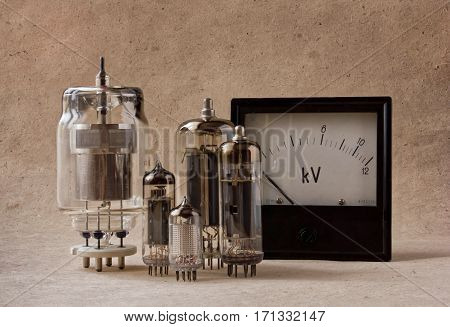electronic background with vintage vacuum tubes and voltmeter on kraft paper