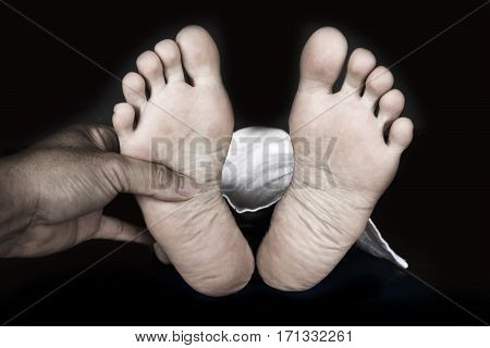 Man Holding Bare Feet Of Woman