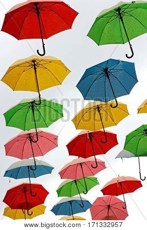 Colorful, hanging umbrellas on white