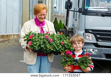 Grandmother with little kid boy after shopping in Greenhouse with colorful blooming geranium flowers. Happy senior woman and her grandson, family having fun together.
