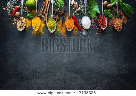 Various herbs and spices on black stone plate