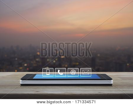 Telephone mobile phone at and email buttons on modern smart phone screen on wooden table over blur of cityscape on warm light sundown Customer support concept