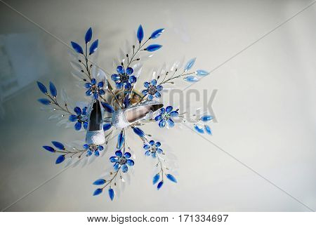 Wedding Shoes Of Bride On Chandelier With Blue Petals.