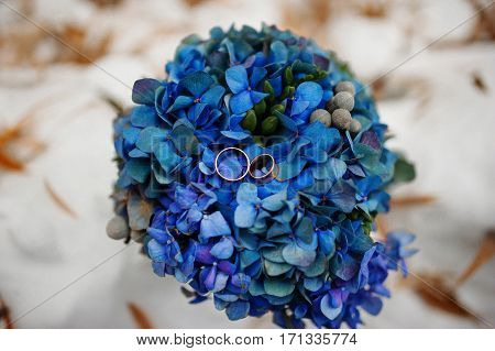 Wedding Rings On Blue Bouquet At Winter Day.