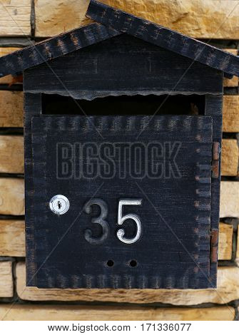 mailbox. Number 35 Iron on stone background