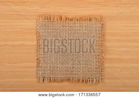 Burlap napkin on wooden background close up