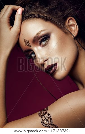 Glamour portrait of beautiful girl model with makeup and romantic hairstyle. Fashion shiny highlighter on skin, sexy gloss lips make-up and dark eyebrows. Gold tatoo.