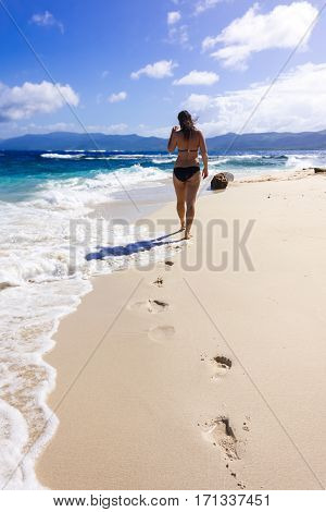 Young woman walks on the beach by shoeless feet, leaving footprints on the send