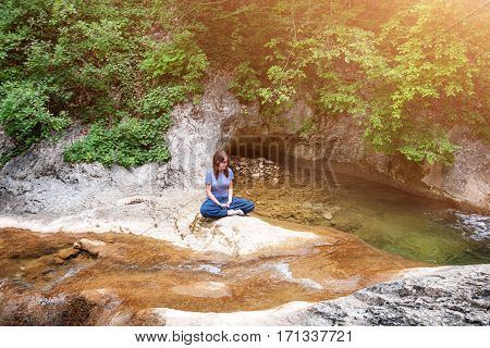 Young woman meditating in lotus position while doing yoga in a wonderful forest near waterfall. Travel, Healthy Lifestyle concept.