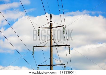 Old power lines. Electricity transmission pylon against the blue sky. High voltage tower.
