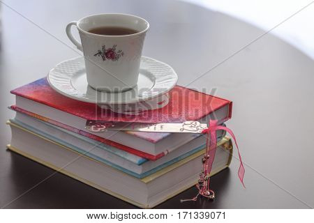 Teacup on colorful books with pink bookmark