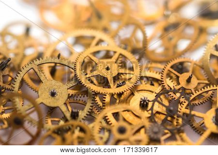 A pile of gears background. Many mechanisms. Old vintage gears. Part of clockwork. The natural color and texture. Focus on front, blurred background. Golden cogs.