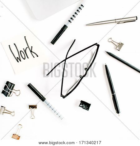 White office desk frame with word Work and supplies. Laptop pen clips glasses and office supplies on white background. Flat lay top view mockup.