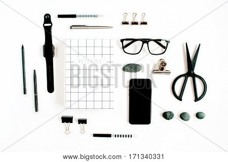 White office desk with supplies. mobile phone glasses notebook scissors and office supplies on white background. Flat lay top view office table desk.