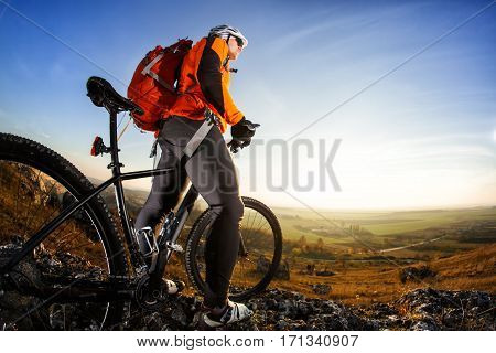 Cyclist man standing on top of a mountain with bicycle and enjoying valley view on a sunny day against a blue sky. Cyclist in the helmet and sunglasses with red backpack. Spring season in the countryside.