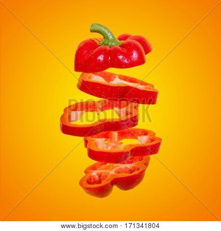 Flying orange paprika. Sliced bell pepper floating on an orange background. Levity vegetable. Capsicum with water drops.