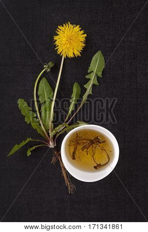 Broth of Dandelion root. Dandelion flower leaves and tea from root on black stone background. Natural medicinal remedy.