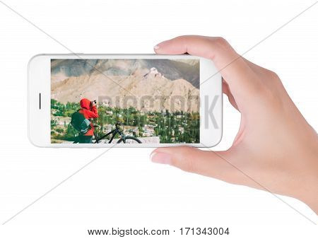 woman using her smartphone for searching the travel information of bike cycling and taking photo in the Himalayan range Leh Ladakh India. Traveling concept isolated on white background.