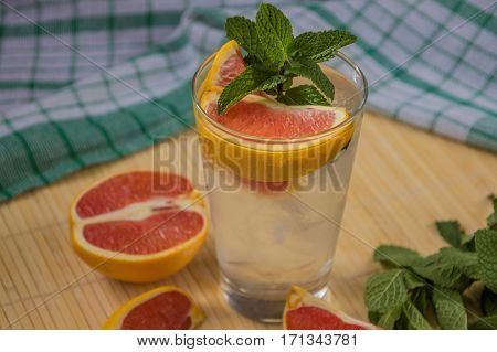Water With Ice, Green Mint And Red Orange In A Glass
