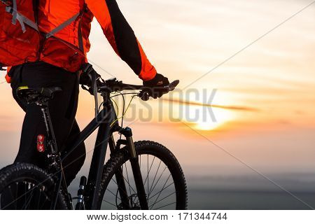 cyclist on mountain-bike at sunset, cyclist on the background of beautiful sunset. cyclist with red backpack. beautiful landscape. back view. horizon. spring season.