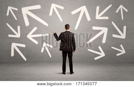 An elegant businessman standing with his back in front of urban wall full of arrows pointing in different directions concept