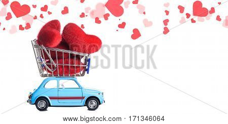 Blue retro toy car delivering craft heart for Valentine's day on white background with flying hearts