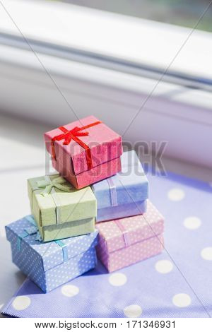 Colorful gift boxes on spotted fabric near window. Spring composition.