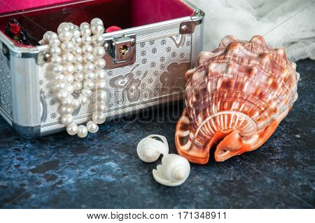 Sea cockleshells (seachells) decoration with pearl on a blue background