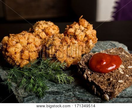 Homemade meat cutlets in batter with parsley, ketchup and bread on stone.