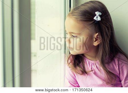 Cute little girl looking through the window