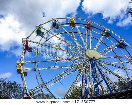 Low angle view of a ferris wheel in an amusement park with a blue sky background. City park ferris wheel in Carousel Gardens Amusement Park New Orleans City Park.