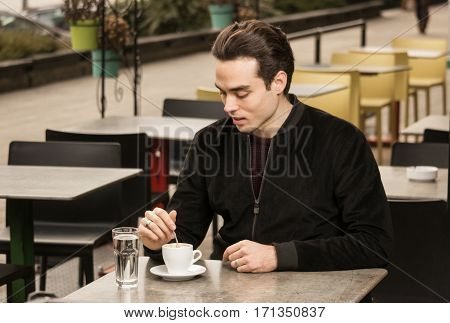 Young Man Stirring Coffee Cup Table