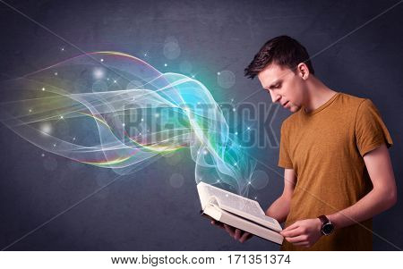 Casual young man holding book with rainbow waves flying out of it