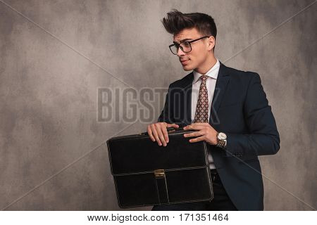 side view of a seated young business man holding briefcase and looking away to a side in studio