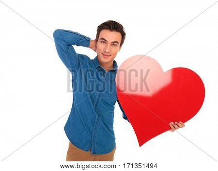 relaxed casual man holding big red heart with hand behind his neck posing on white background