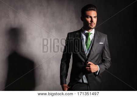 side view picture of an elegant man in tuxedo jacket buttoning his coat and looks away in studio with copy space