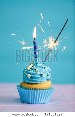 Birthday cupcake with candle and sparkler on color background