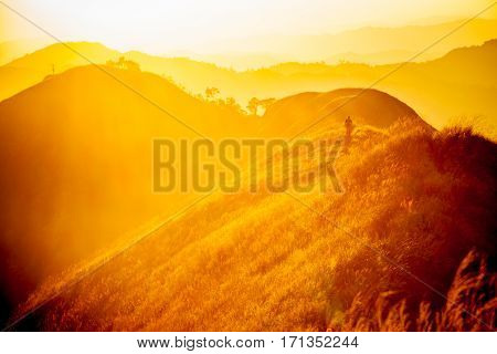 Dramatic sunset with traveler standing on hill