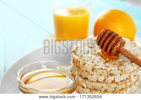 Closeup of tasty rice wafers with honey and glass of orange juice