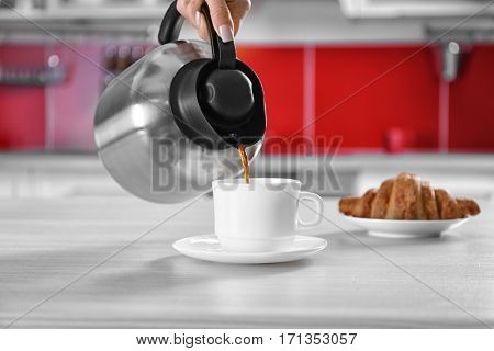 Pouring coffee from thermos kettle into cup on kitchen counter