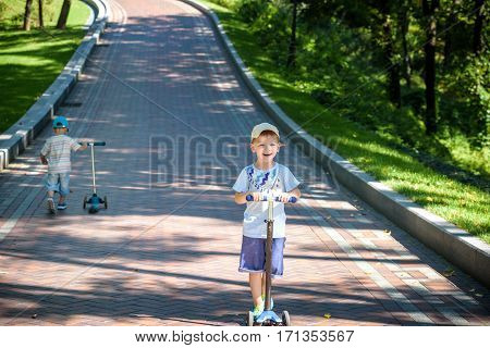 Two Cute Boys, Compete In Riding Scooters, Outdoor In The Park, Summertime.