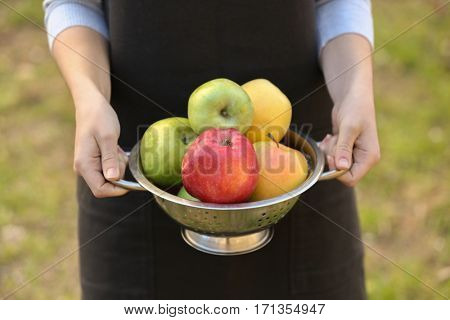Female hands holding colander with fruits, closeup